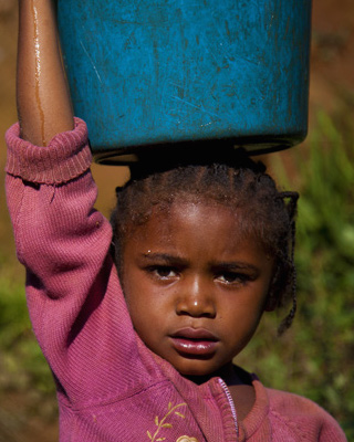 Girl carrying water bucket on her head