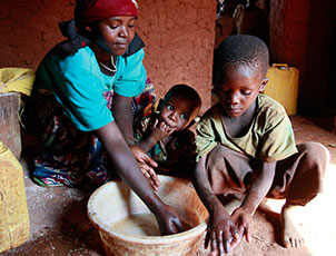 Mother - Patricia Umariya, Elisa Niyonsenga, Jean Damacene, Gatora village, Bugesera district. Rwanda. 24th August 2011. Picture: WaterAid / Zute Lightfoot